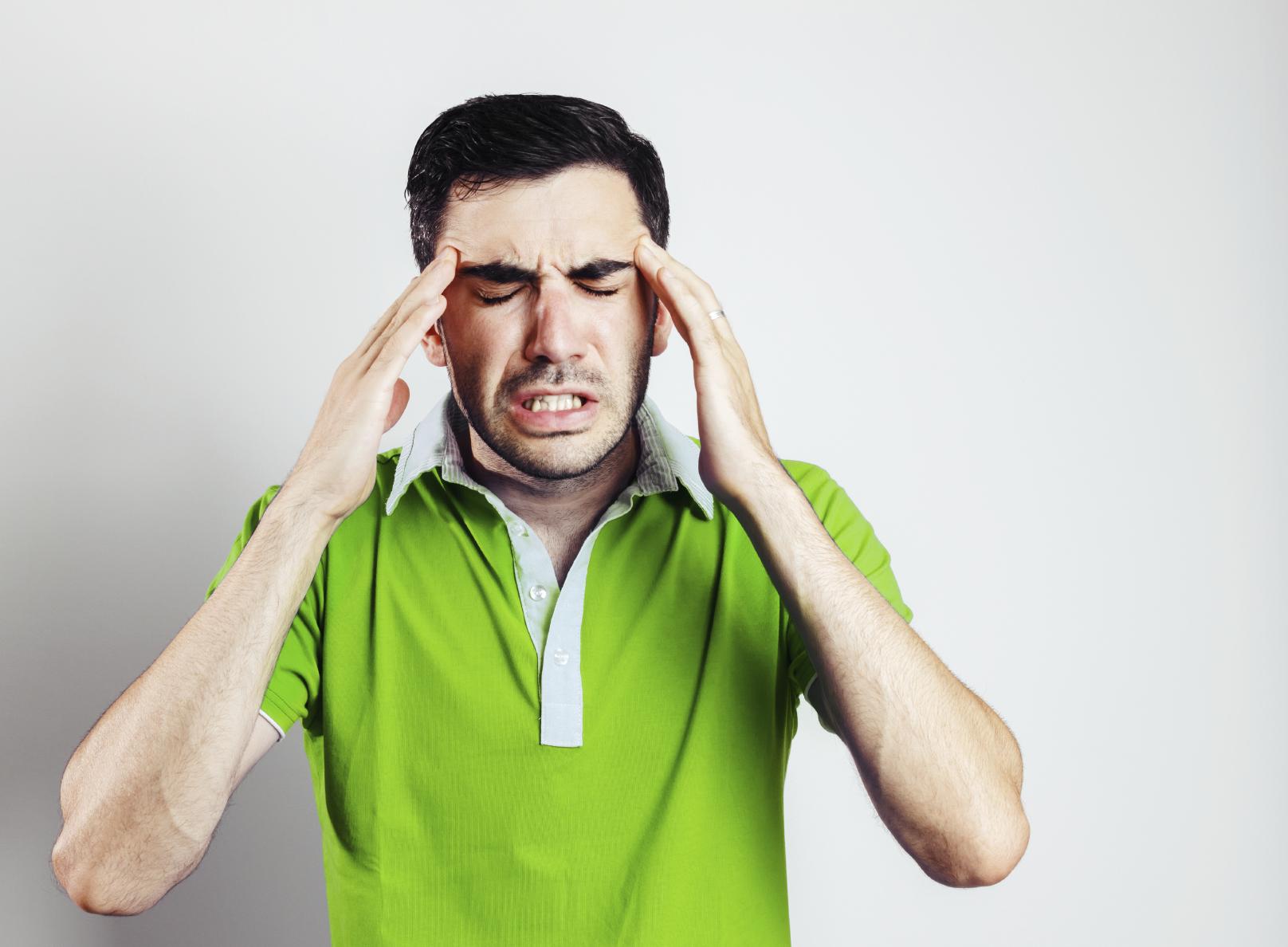 Portrait of young man wearing green shirt having head pain